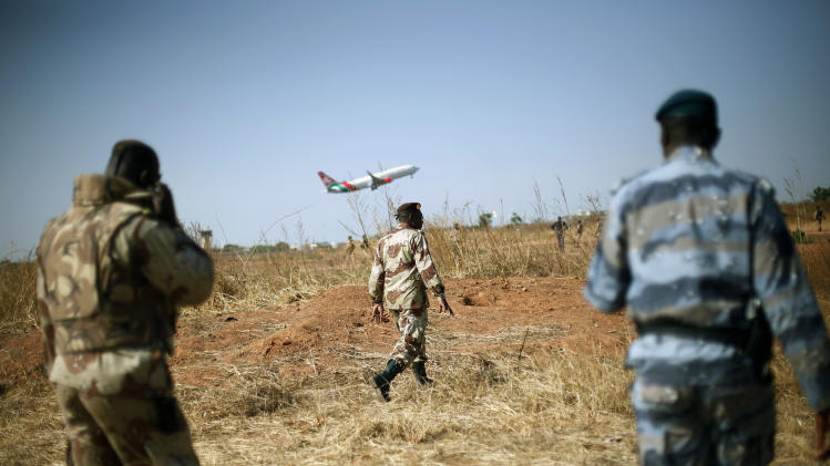 "Mali National Guard soldiers stand guard on the military side of  Bamako's airport Wednesday Jan. 16, 2013,  as a commercial jet takes off during a joined visit to French and Malian troops by Mali's President  Dioncounda Traore and French Ambassador to Mali  Christian Rouyer. French troops pressed northward in Mali toward territory occupied by radical Islamists on Wednesday, military officials said, announcing the start of a land assault that will put soldiers in direct combat ""within hours.""(AP Photo/Jerome Delay)"