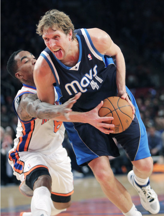 Dallas Mavericks' Dirk Nowitzki, right, is fouled by New York Knicks' J.R. Smith during the second half of an NBA basketball game in New York, Sunday, Feb. 19, 2012. The Knicks defeated the Mavericks