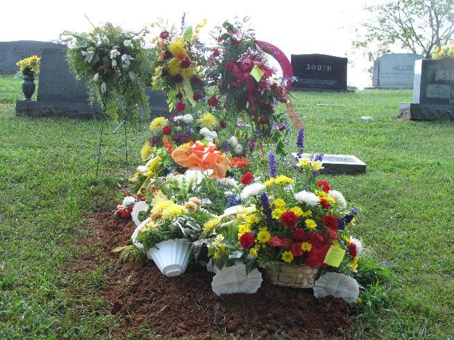 Flowers cover the grave of career lawman Herbert Proffitt on Wednesday, Sept. 5, 2012, at Tompkinsville, Ky.Proffitt was fatally shot outside his home on Aug. 28, and a man he arrested years ago is charged with murder in the case. (AP Photo/Bruce Schreiner)