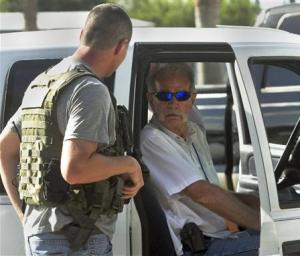 Pastor Terry Jones talks to a member of the Polk County Sheriff's Department as he sits in his vehicle prior to his arrest in Mulberry