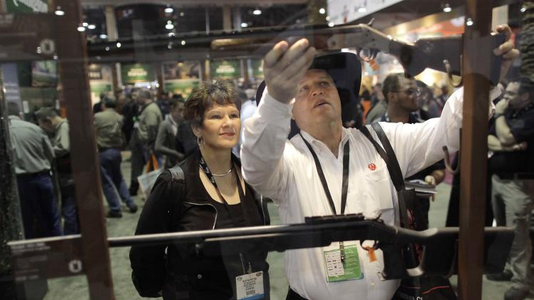 Industry exhibitors and retailers look over various hunting rifles at the Shooting, Hunting and Outdoor Trade show, Tuesday, Jan. 18, 2011, in Las Vegas. (AP Photo/Julie Jacobson)