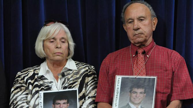 Josephine and Alfred Acquaviva, of Wayne, New Jersey, wear photographs of their late son Paul as they listen to a press conference at the end of pre-trial hearings for the five Guantanamo prisoners accused of orchestrating the Sept. 11, 2001 terrorist attacks, inside the Camp Justice compound on the Guantanamo Bay U.S. Naval Base in Cuba, Friday, Oct. 19, 2012. Paul died at age 29 in the World Trade Center attack. The five defendants face charges that include terrorism and murder for allegedly planning and helping to carry out the Sept. 11, 2001, hijacking plot. They could get the death penalty if convicted. (AP Photo/Toronto Star, Michelle Shephard, Pool)