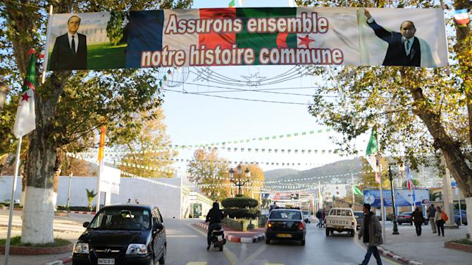 """Cars drive under a banner reading """"Accepting together our common history"""" Wednesday, Dec.19, 2012 in Tlemcen, northwest Algeria. French President Francois Hollande is hoping for a clean start and an end to tensions with Algeria during a state visit to the country that was once the French empire's most-prized colony. The two-day state visit by the Socialist president, which begins Wednesday, comes as Algeria celebrates 50 years since its independence from France after a brutal seven-year war — and 130 years of colonial rule. Hollande will travel to Algiers and Tlemcen. (AP Photo/Nadji)"""