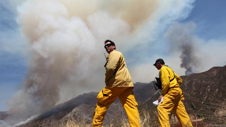 Los Angeles County Fire Department firefighters, Mitch Brookhyser, left, and Denis Cross survey the Williams Fire burning in the San Gabriel Mountains in the Angeles National Forest near Glendora, Calif., Tuesday, Sept. 4, 2012. A 3,600-acre brush fire continued to burn in the Angeles National Forest about 25 miles northeast of downtown Los Angeles on Tuesday as crews worked in the steep, rugged terrain to bring the blaze under control. The fire was about 15 percent contained and officials said it could take a week to bring it under control. (AP Photo/Damian Dovarganes)