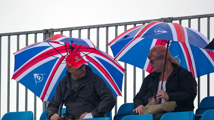 Race watchers take shelter during practice at the Silverstone circuit, England, Friday, July 6, 2012. The Formula 1 teams make preparations ahead of the British Grand Prix at Silverstone circuit on Sunday. (AP Photo/Tom Hevezi)