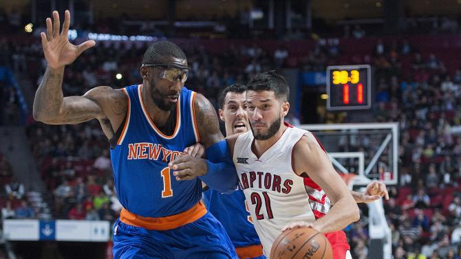 Toronto Raptors' Greivis Vasquez (21) drives to the net as New York Knicks' Amare Stoudemire defends during first-quarter NBA preseason basketball game action in Montreal, Friday, Oct. 24, 2014. (AP Photo/The Canadian Press, Graham Hughes)
