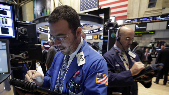 Traders Richard Scardino, left, and Luigi Muccitelli work on the floor of the New York Stock Exchange Tuesday, Oct. 22, 2013. Stocks gained in early trading Tuesday as investors bet that the Federal Reserve would keep up its economic stimulus for longer after the government reported a slowdown in hiring last month. (AP Photo/Richard Drew)