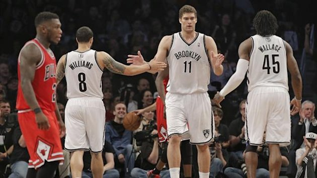 Brooklyn Nets guard Deron Williams (8), center Brook Lopez (11) and forward Gerald Wallace (45) tap hands as Chicago Bulls point guard Nate Robinson walks off the court (Reuters)