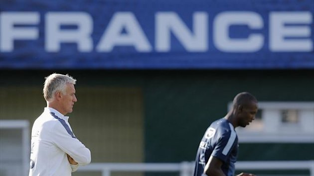 France's national team coach Didier Deschamps (L) watches player Eric Abidal during a training session at Clairefontaine, near Paris, August 12, 2013 (Reuters)