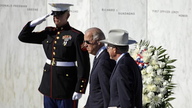 Vice President Joe Biden, center, and Interior Secretary Ken Salazar, right, walk in front of The Wall of Names, containing the names of the 40 passengers and crew of Flight 93, as they arrive for a memorial service at the Flight 93 National Memorial in Shanksville, Pa., Tuesday, Sept. 11, 2012. (AP Photo/Gene J. Puskar)