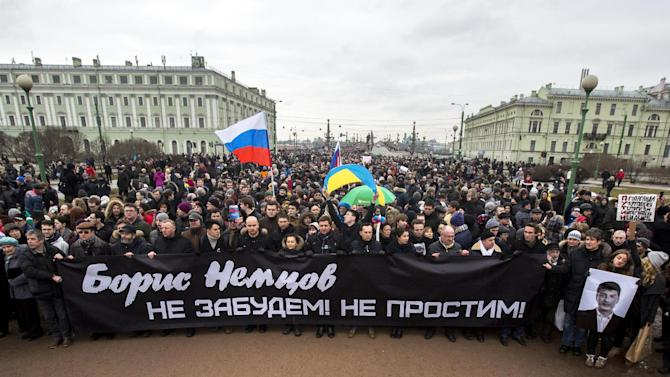 People carry a banner reading ' Boris Nemtsov, we will never forget, we will never forgive' as they march in memory of opposition leader Boris Nemtsov who was gunned down on Friday, Feb. 27, 2015 near the Kremlin,  in St.Petersburg, Russia, Sunday, March 1, 2015.  Some thousands converged Sunday in central Moscow to mourn veteran liberal politician Boris Nemtsov, whose killing on the streets of the capital has shaken Russia's beleaguered opposition.   (AP Photo/Elena Ignatyeva)