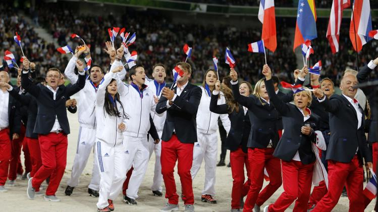 France's team celebrates and waves to supporters during the opening ceremony of the world Equestrian Games at the d'Ornano stadium in Cae