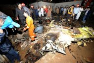 Pakistani rescue workers and local residents search the site of a plane crash in Rawalpindi. The Bhoja Air flight from Karachi burst into flames after coming down in fields near a village on the outskirts of the Pakistani capital as it tried to land in rain and hail at the city&#39;s international airport
