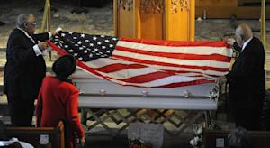 A flag is draped over the casket of Jayvon Felton during …