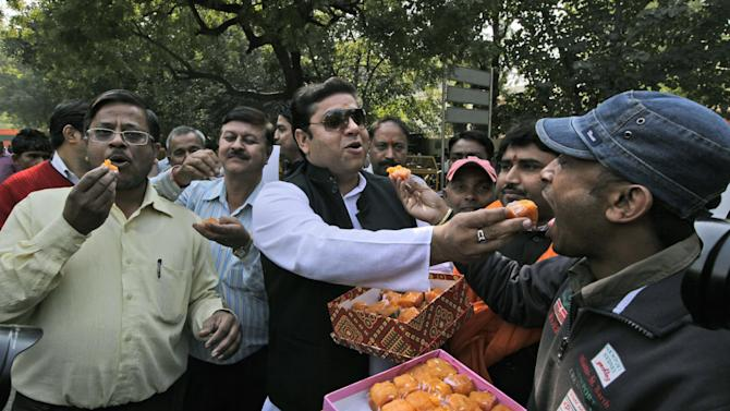Activists of Bajarang dal, a Hindu rights group, distribute sweets to celebrate Mohammed Ajmal Kasab's execution, in New Delhi, India, Wednesday, Nov. 21, 2012. India executed the lone surviving gunman from the 2008 terror attack on Mumbai early Wednesday, the country's home ministry said. Kasab, a Pakistani citizen, was one of 10 gunmen who rampaged through the streets of India's financial capital for three days in November 2008, killing 166 people.  (AP Photo/ Manish Swarup)