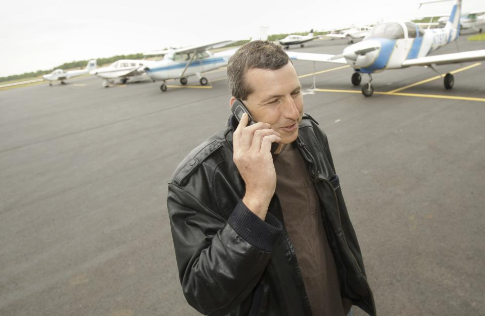 Commercial pilot Bill Phillips uses his cellphone on the tarmac at North Little Rock municipal Airport in North Little Rock, Ark., Wednesday, April 20, 2011. Phillips is representative of a trend of abandoning landline phones in favor of cellphones. (AP Photo/Danny Johnston)