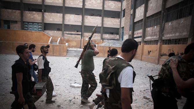 FSA soldiers go to the front line in Izaa district in Aleppo, Syria, Sunday, Sept. 9, 2012. On Friday, U.S. Senators John McCain, Joe Lieberman and Lindsay Graham, who have toured the volatile Middle East in recent days, urged Washington to help arm Syria's rebels with weapons and create a safe zone inside the country for a transition government. (AP Photo/ Manu Brabo)