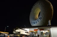Space shuttle Endeavour is seen behind Randy's Donuts, an L.A. landmark on Manchester Blvd., Oct. 12, 2012.