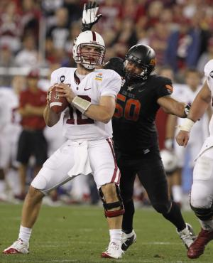 Stanford quarterback Andrew Luck (12)  looks downfield just before getting sacked by Oklahoma State defensive end Jamie Blatnick (50) during the second half of the Fiesta Bowl NCAA college football game Monday, Jan. 2, 2012, in Glendale, Ariz. (AP Photo/Ross D. Franklin)