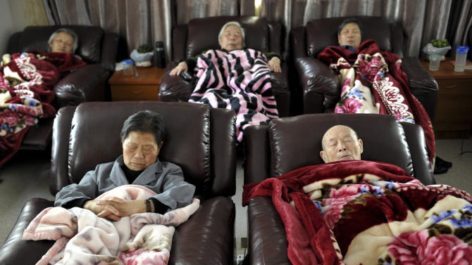 FILE - In this Tuesday April 10, 2012, file photo, elderly people take a nap at a day care center in Shanghai, China. Nursing homes are not an option for most Chinese. The few nursing homes in China supply only 22 beds for every 1,000 seniors, and most are too expensive for the average family. Even children who can afford nursing homes fear sending their parents away will mark them as unfilial. (AP Photo/File)