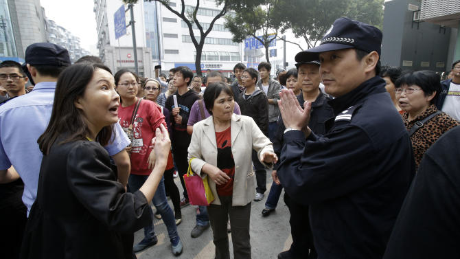 A Chinese police officer gestures as residents confront him in Zhejiang province's Ningbo city, protesting the proposed expansion of a petrochemical factory Sunday, Oct. 28, 2012. Thousands of people in the eastern Chinese city clashed with police Saturday while protesting the proposed expansion of the factory that they say would spew pollution and damage public health, townspeople said. (AP Photo/Ng Han Guan)