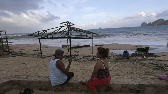 Residents sit on Medano beach before the possible arrival of Tropical Storm Polo in Cabo San Lucas, after Hurricane Odile hit Baja California
