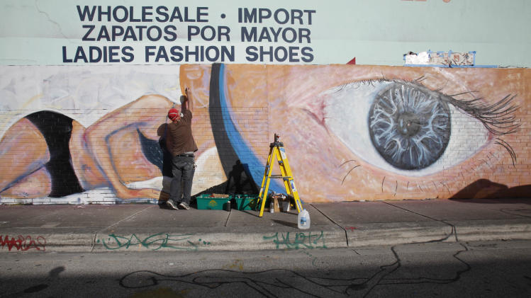 Artist Scott Debus spray-paints a mural on the wall of a warehouse in the Wynwood district of Miami, Monday, Dec. 3, 2012. Art Basel Miami Beach and about two dozen other independent art fairs open Thursday. Tens of thousands of people are expected through Sunday at the fairs throughout Miami and South Beach. (AP Photo/Wilfredo Lee)