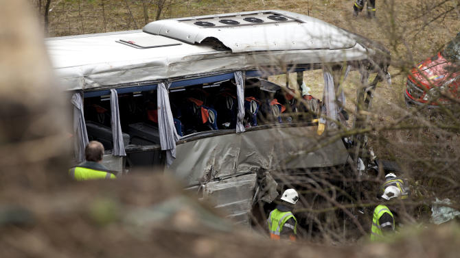 Emergency services attend the scene of a bus crash in Ranst, Belgium, on Sunday, April 14, 2013.  A Poland registered bus carrying Russian youngsters crashed through highway guardrails and into a field below, near the port city of Antwerp on Sunday, killing at least five people and leaving five more critically injured. (AP Photo/Virginia Mayo)