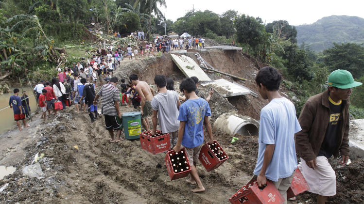 People carry their merchandise on a muddy part of the collapsed road in suburban Antipolo City, east of Manila, Philippines, Thursday, Aug. 9, 2012. The road collapsed at the height of the rain yesterday as a fresh deluge forced more evacuations along fast-rising rivers in the Philippine capital Thursday, as the city and surrounding areas struggled to deal with widespread flooding triggered by nearly two weeks of relentless rains. (AP Photo/Pat Roque)