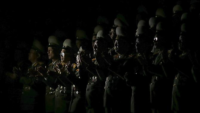 Senior North Korean military officers are lit by light from a camera as they follow the performance on Pyongyang's main Kim Il Sung Square celebrating the 70th anniversary of the founding of the ruling Workers' Party of Korea