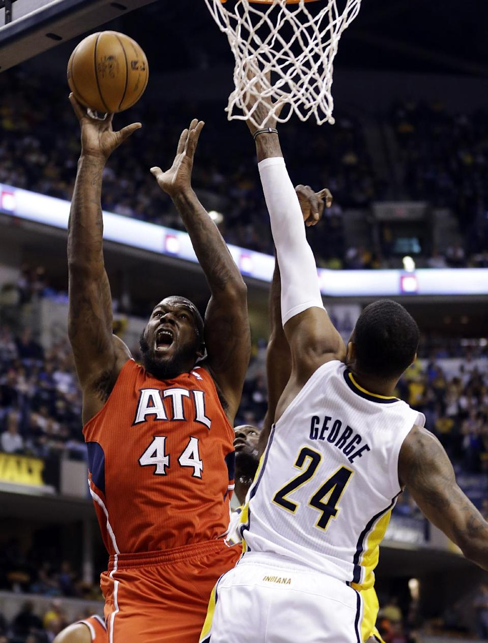 Atlanta Hawks forward Ivan Johnson (44) shoots over Indiana Pacers forward Paul George in the first half of Game 2 of a first-round NBA basketball playoff series in Indianapolis, Wednesday, April 24, 2013. (AP Photo/Michael Conroy)