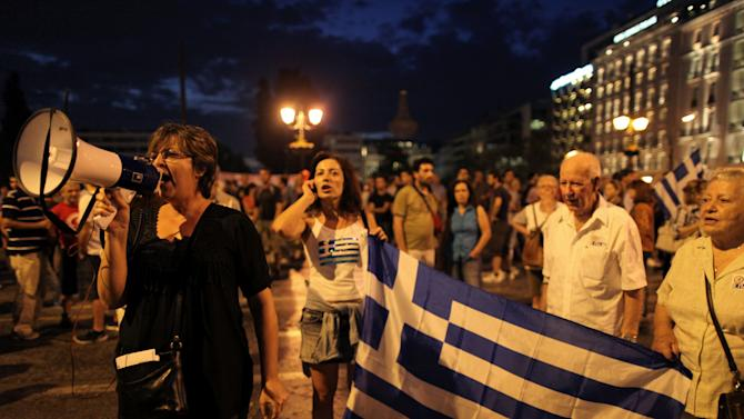 Protesters hold a Greek flags as another  uses a loudspeaker, during a union anti-austerity rally a day before the visit by German Chancellor Angela Merkel  in Athens on Monday, Oct. 8, 2012. Greek police have increased security and are preparing to close down large sections of the capital Athens to contain protests against Germany's Chancellor, Angela Merkel, who is visiting the city Tuesday for talks with the country's Prime Minister Antonis Samaras.(AP Photo/Petros Giannakouris)