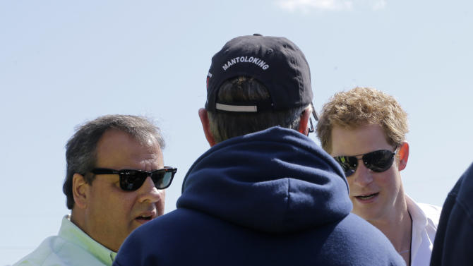 Britain's Prince Harry, right, and New Jersey Gov. Chris Christie, left, greet a Mantoloking firefighter while visiting the area hit by Superstorm Sandy, Tuesday, May 14, 2013, in Mantoloking. Prince Harry began a tour  of New Jersey's storm-damaged coastline, inspecting dune construction, walking past destroyed homes and shaking hands with police and other emergency workers.  New Jersey sustained about $37 billion worth of damage from the storm. (AP Photo/Mel Evans, Pool)