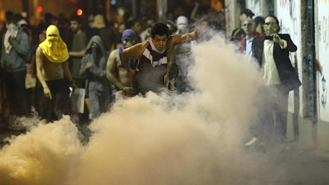 FILE - This June 17, 2013 photo, a protester kicks a gas canister during a demonstration a in Rio de Janeiro, Brazil. Thousands took to the streets in largely peaceful protests in at least eight cities in Brazil Monday, demonstrations that voiced the deep frustrations Brazilians feel about carrying heavy tax burdens but receiving woeful returns in public education, health, security and transportation. Officers in Rio fired tear gas and rubber bullets when a group of protesters invaded the state legislative assembly and later vandalized and looted properties in the area.(AP Photo/Victor R. Caivano, File)