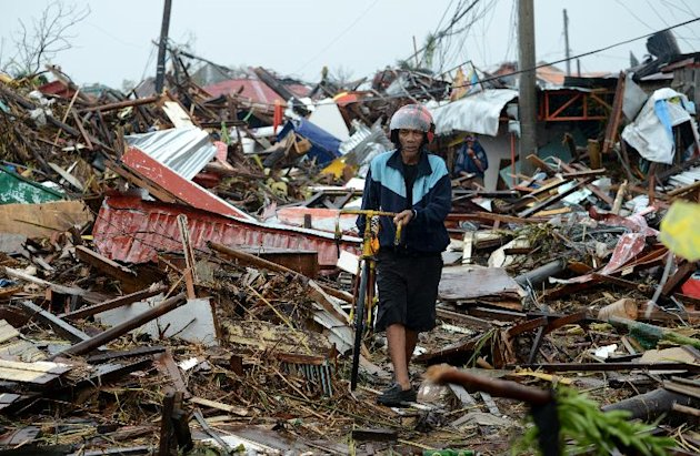 A man walks past debris of destroyed houses in Tacloban, eastern island of Leyte on November 10, 2013