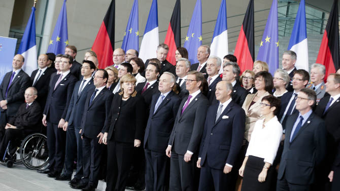 French President Francois Hollande, center left, and German Chancellor Angela Merkel, center, pose with their governments for a group photo at the chancellery in Berlin, Tuesday, Jan. 22, 2013. The governments meet as part of events marking the 50th anniversary of the signing of the Elysee Treaty, a landmark accord cementing reconciliation between the two European powers. (AP Photo/Markus Schreiber)