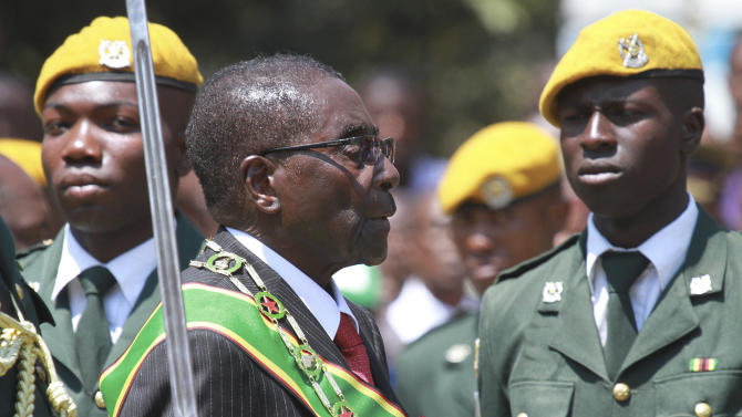 """FILE - In this file photo taken Tuesday, Sept. 17, 2013 Zimbabwean President Robert Mugabe inspects the guard of honor during the opening of the first session of the eighth Parliament of Zimbabwe in Harare. Zimbabwe's longtime President Robert Mugabe says he doesn't want anyone to be fooled by his impeccable Western style of dress and his precise, teacherly use of English: He is African through and through. """"I am not British, I am not a colonial product because I am a complete Zimbabwean, """" he told graduates at Great Zimbabwe University near the remains of the 13th Century walled city, for which Zimbabwe, the former colony of Rhodesia, is named. (AP Photo/Tsvangirayi Mukwazhi-file)"""