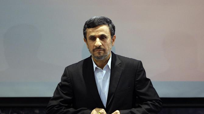 "Iranian President Mahmoud Ahmadinejad adjusts his jacket as he listens to the Iranian national anthem at the start of a press conference in Tehran, Iran, Tuesday, Oct. 2, 2012. Ahmadinejad blamed the steep drop in Iran's currency Tuesday to ""psychological pressures"" linked to Western sanctions over Tehran's nuclear program. The remarks were part of his attempt to deflect criticism from political rivals that his government's policies also have contributed to the nosedive of the Iranian rial, which has lost more than half its value against the U.S. dollar this year and has sharply pushed up costs for many imported goods. (AP Photo/Vahid Salemi)"