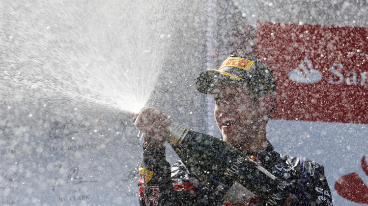 Red Bull driver Sebastian Vettel of Germany sprays with champagne during the German Formula One Grand Prix at the Nuerburgring racetrack, in Nuerburg, Germany, Sunday, July 7, 2013. (AP Photo/Michael Probst)