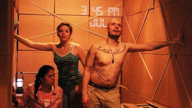 "This theater publicity image released by DDPR Public Relations shows cast members during a performance of ""LaRuta.""  The off-Broadway company Working Theater is presenting a play about immigrants sneaking across the border is being staged inside a 48-foot-long cargo container. (AP Photo/DDPR Public Relations, Lia Chang)"