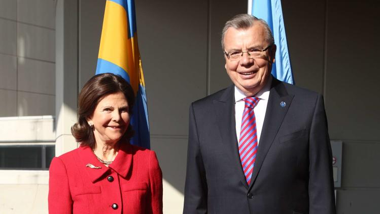 Queen Silvia of Sweden and UNODC Executive Director Fedotov pose for photographs before a drugs conference in Vienna