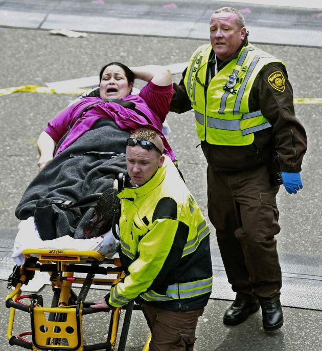 Medical workers aid an injured woman at the finish line of the 2013 Boston Marathon following two explosions there, Monday, April 15, 2013 in Boston. Two bombs exploded near the finish of the Boston M