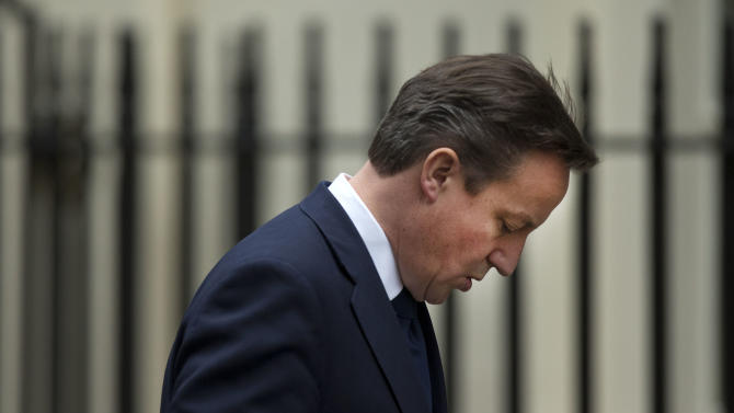 Britain's Prime Minister David Cameron walks back to number 10 through Downing Street in London, after arriving back from Prime Minister's Question at the Houses of Parliament, Wednesday, Nov. 28, 2012.  The judge who spent a year investigating the misdeeds of Britain's lively newspapers is giving Prime Minister David Cameron an early look at his recommendations for the regulation of the press.  Officials say Cameron will get a copy of Lord Justice Brian Leveson's report Wednesday, a day before the public sees it, but Cameron is already being besieged with advice about how to respond to the still-secret recommendations.  (AP Photo/Matt Dunham)