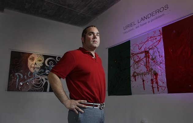 In this Oct. 23, 2012 photo, James Perez, owner of Cueto James Art Gallery, poses between pieces titled &quot;Ego&quot;, left, and &quot;Legalize Drugs&quot;, right, that will be in the show titled &quot;Uriel Landeros: Houston We Have a Problem&quot; in Houston. Uriel Landeros, is the man accused of vandalizing a Picasso painting at the Menil with spray paint in June. (AP Photo/Houston Chronicle, Melissa Phillip)