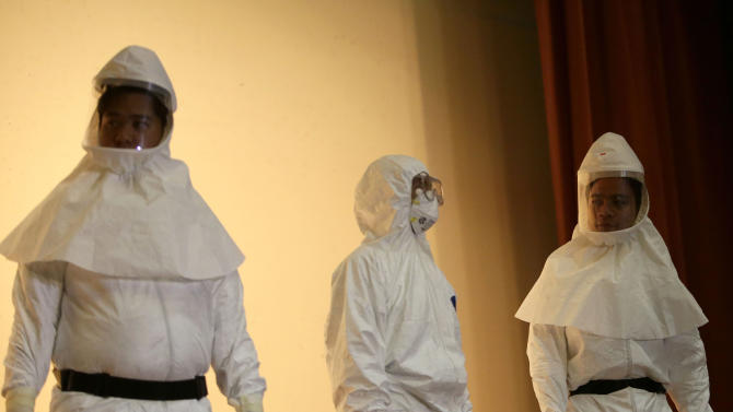 "Medical health workers show different ""Ebola suits"" during a media tour of the Research Institute for Tropical Medicine facility to show the Government's readiness in the still Ebola-free country Tuesday, Oct. 21, 2014 at Alabang, Muntinlupa city, south of Manila, Philippines. (AP Photo/Bullit Marquez)"