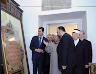 "A handout picture released by the official Syrian Arab News Agency (SANA) shows Syrian President Bashar al-Assad looking at Islamic scripture during a visit to the al-Amawi mosque in Damascus on March 20. China on Wednesday hailed a UN statement on Syria as a positive step towards a political settlement and called on Assad's government to ""cease violence immediately"""