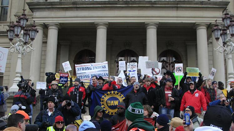 Thousands of protesters gather for a rally on the State Capitol grounds in Lansing, Mich., Tuesday, Dec. 11, 2012. The crowd is protesting right-to-work legislation that was passed by the state legislature last week.  Michigan will become the 24th right-to-work state, banning requirements that nonunion employees pay unions for negotiating contracts and other services. (AP Photo/Carlos Osorio)