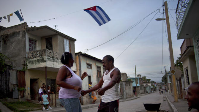 A couple dance in the streets of Guantanamo, Cuba, on the eve of the country's Revolution Day, Wednesday, July 25, 2012. Revolution Day marks the July 26, 1953 rebel attack led by Fidel and Raul Castro on the Moncada military barracks. The attack is considered the beginning of the revolution that culminated with dictator Fulgencio Batista's ouster.  (AP Photo/Ramon Espinosa)