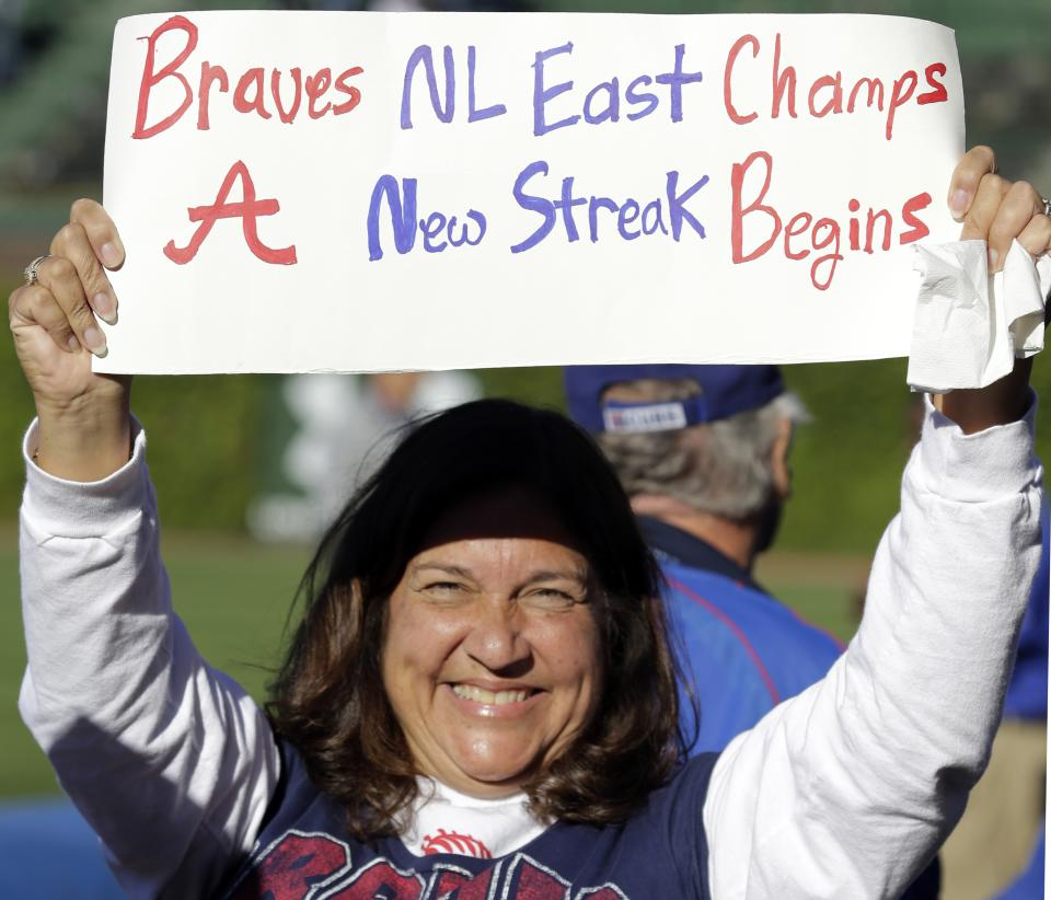 Atlanta Braves fan Terri Elias, from Atlanta, holds a sign after the Braves defeated the Chicago Cubs 5-2 in a baseball game in Chicago, Sunday, Sept. 22, 2013. The Braves clinched the NL East as the Washington Nationals lost to the Florida Marlins. (AP Photo/Nam Y. Huh)