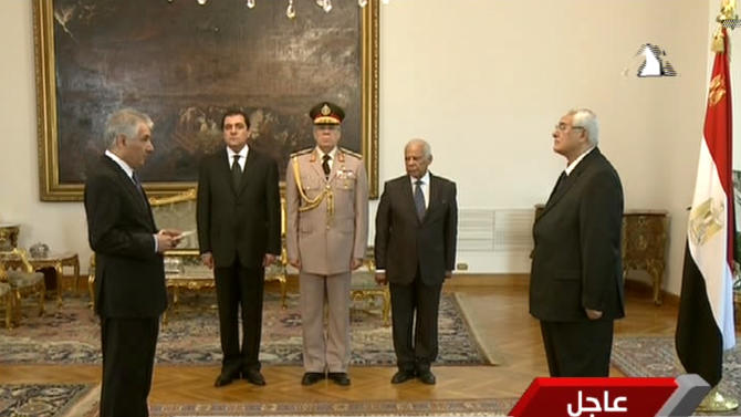 This image made from state television shows Egypt's interim President Adly Mansour, right, swearing in Ahmed Galal, left, as finance minister in Cairo, Tuesday, July 16, 2013. Egypt's interim president on Tuesday swore in the first Cabinet since the military ousted the Islamist president, giving members of the country's liberal movements key positions. The Cabinet includes three women.(AP Photo/Egyptian State Television)